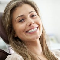 A bright toothy smile and eye contact from a pretty young woman proud to show off her perfect teeth while sitting in a dentist's chair.